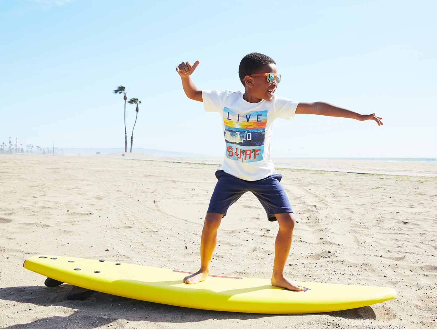 Photo of a boy wearing cool childrens clothes on surfboard